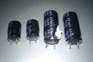 The 220 µF capacitors on the left have noticeable wavy cases from internal pressure buildup, while the 1000 µF capacitor in the middle has actually blown its plug out of the bottom of its case.